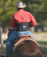 Man on a horse wearing a neoprene back support.